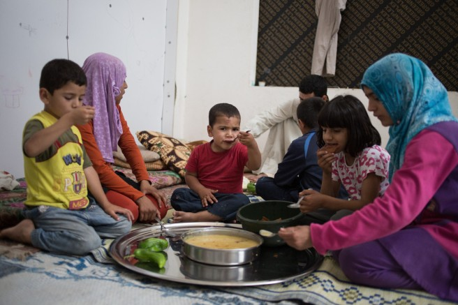 A Syrian family eats together in their home in the Al Waha Commercial Centre, an abandoned shopping centre in Dede Al Koura near the city of Tripoli. The residents live with few possessions in bare, tiled rooms that used to be shops. The centre is currently home to some 90 Syrian families and has been connected to a nearby municipal water tower with an erratic water supply.